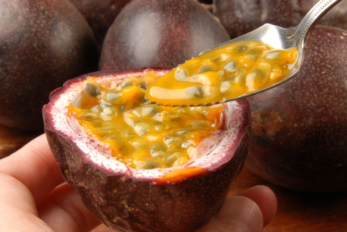 Halved passion fruit with spoon scooping fruit flesh.
