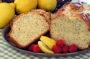 Sliced poppy seed cake garnished with lemon wedges and raspberries.